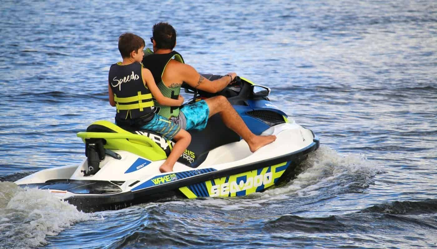 Father and son riding personal watercraft