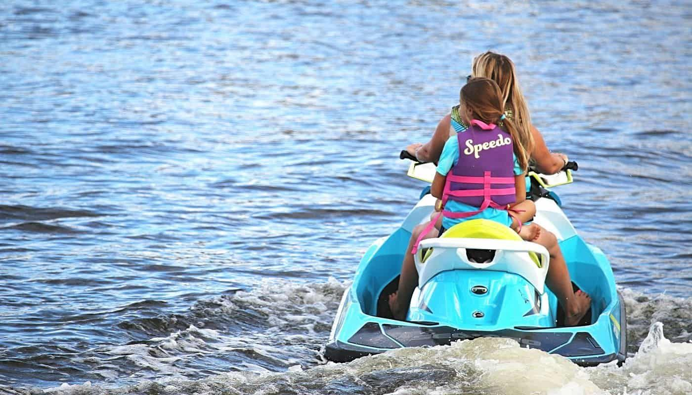 Mother and daughter riding personal watercraft
